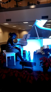 playing at a white piano