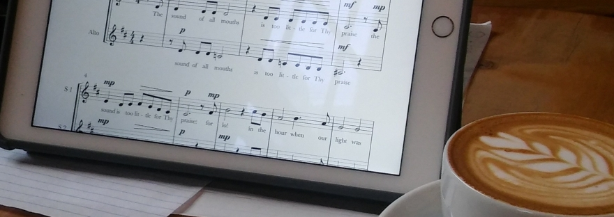 score for choir composition on tablet sitting next to latte art